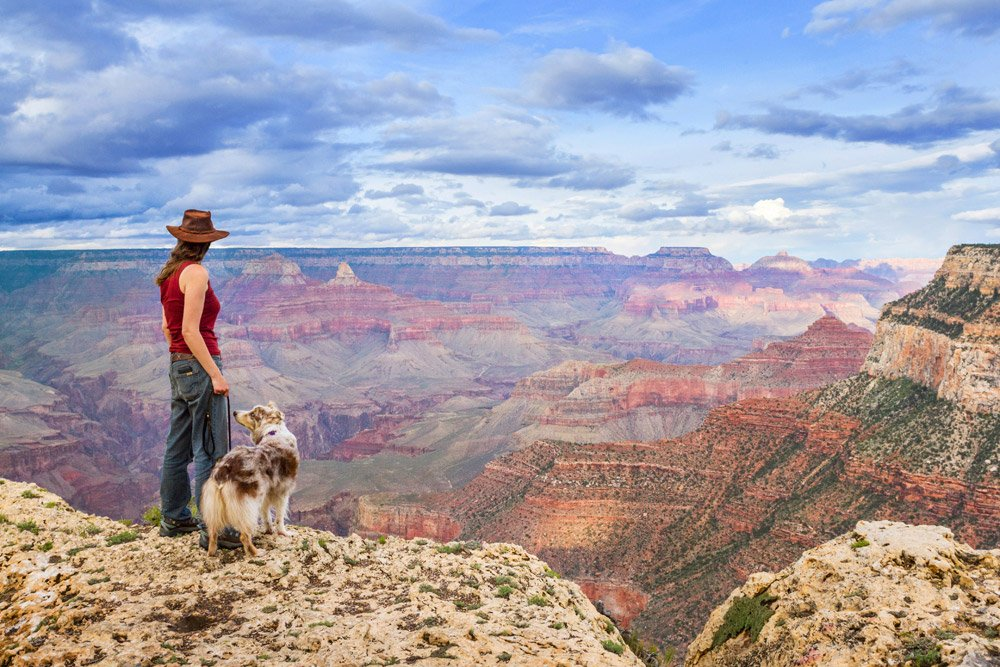 girl and dog looking out at the Grand Canyon